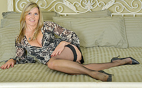 Huge-chested Light-haired Cougar Wearing Stockings And High-heeled Shoes Is Fondling Her Great Leg