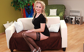 Steamy Ash-blonde Mature Wearing Black Lingerie And High-heeled Slippers Is Sitting On Couch